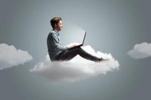 Mann arbeitet an seinem Notebook auf einer Wolke