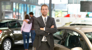 erfolgreicher Geschftsmann im Autohandel - im Hintergrund Kunden & Interieur des Autohauses // successful businessman in the car trade - in the background customer & interior of the car dealership